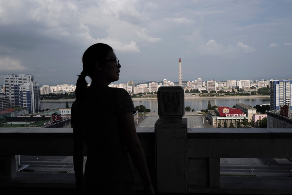 In this July 16, 2019, photo, a woman stands against the 170-meter-tall Tower of Juche Idea, center, in Pyongyang, North Korea. The word Juche is spla...