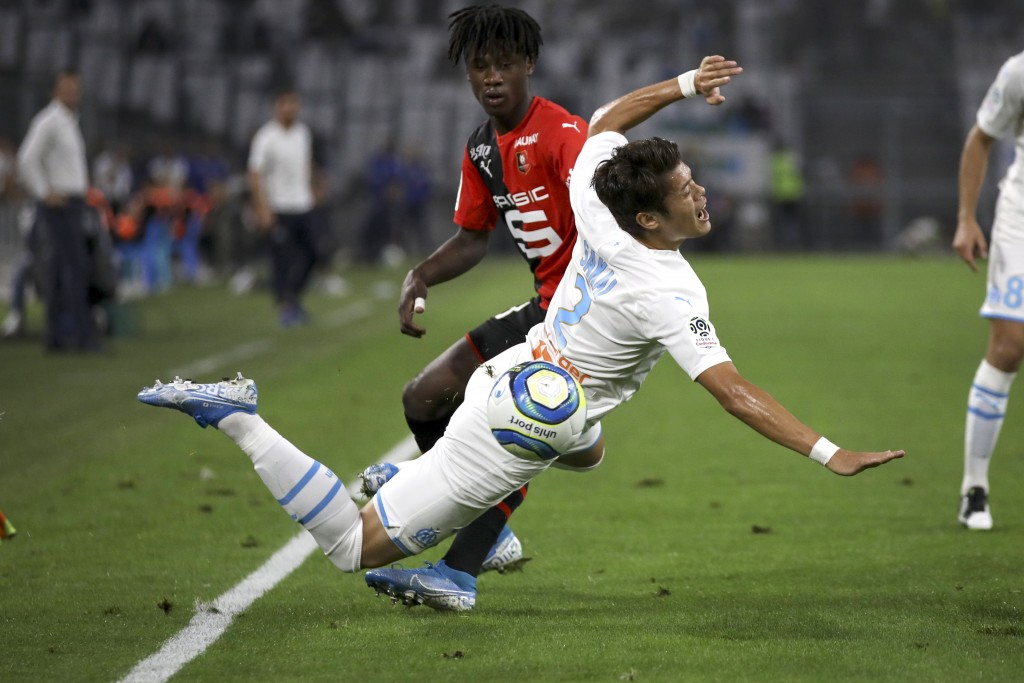 Marseille's Hiroki Sakai falls to the ground while battling for the ball with Rennes' Eduardo Camavinga during the French League One soccer match betw...