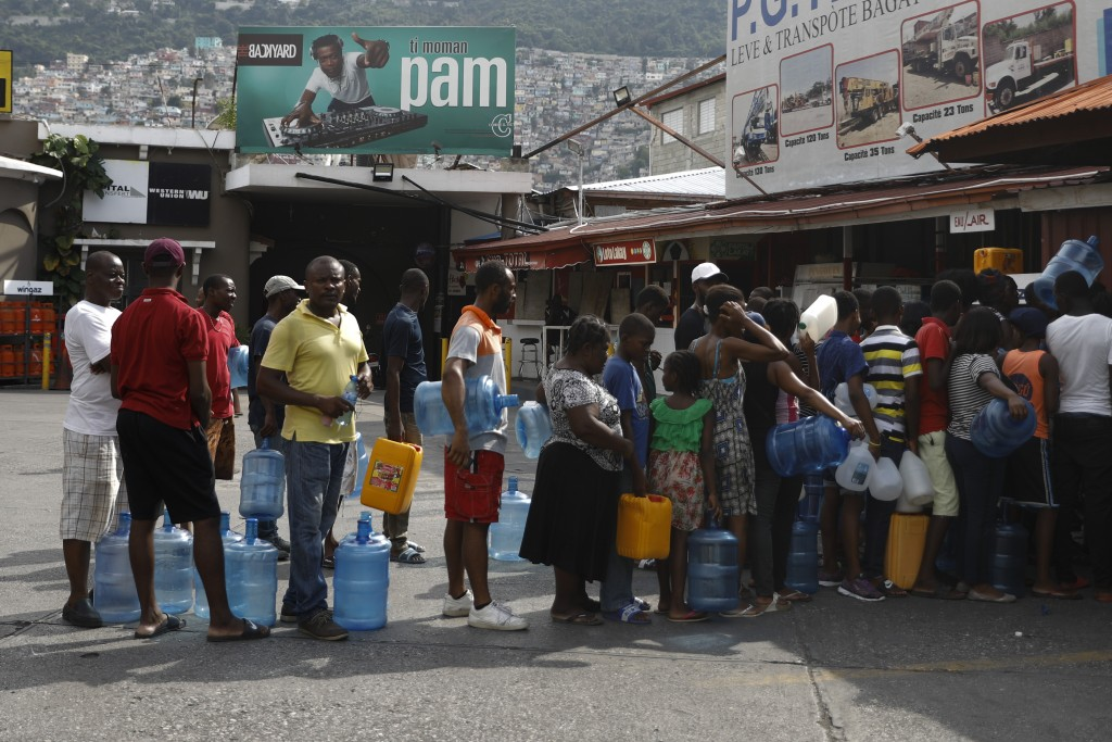 People wait in line to buy drinking water from an open business, in Port-au-Prince, Haiti, Sunday, Sept. 29, 2019. Hundreds of people stood in line al...