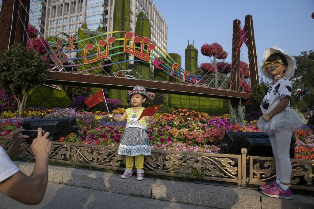 In this Saturday, Sept. 28, 2019, photo, Chinese children pose with Chinese national flags near a floral display for the upcoming 70th anniversary of ...