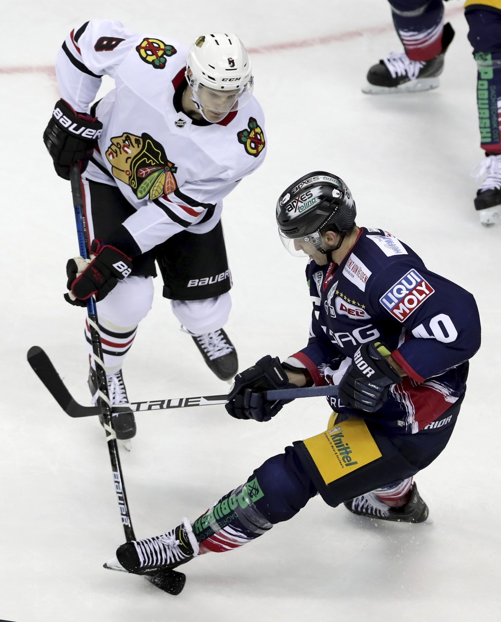 Berlin's Maxim Lapierre, right, steps on the stick of Chicago's Dominik Kubalik, left, during a NHL Global Series ice hockey game between Eisbaeren Be...
