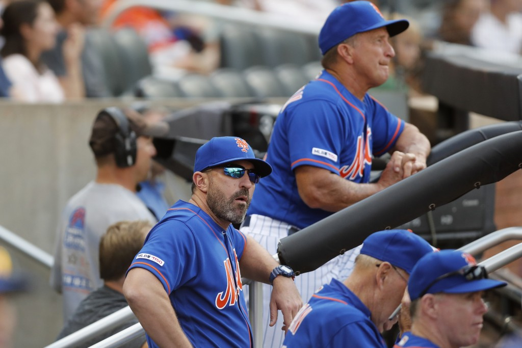 New York Mets manager Mickey Callaway, front left, looks from the dugout during a baseball game against the Atlanta Braves, Sunday, Sept. 29, 2019, in...