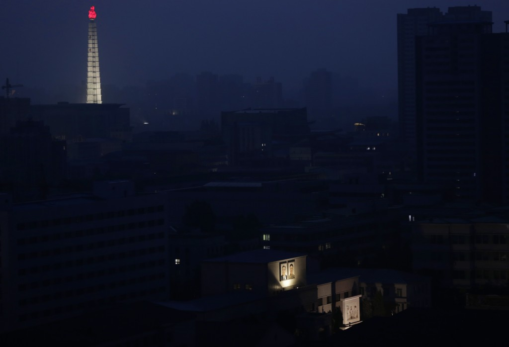 FILE - In this June 19, 2018, file photo, portraits of the late North Korean leaders Kim Il Sung and Kim Jong Il are illuminated on a building as the ...