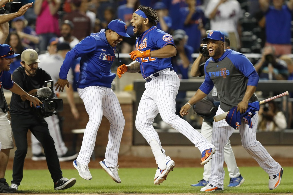 New York Mets' Marcus Stroman, left, leaps with Dominic Smith (22) as Robinson Cano watches after Smith hit a walk-off, solo home run in a baseball ga...