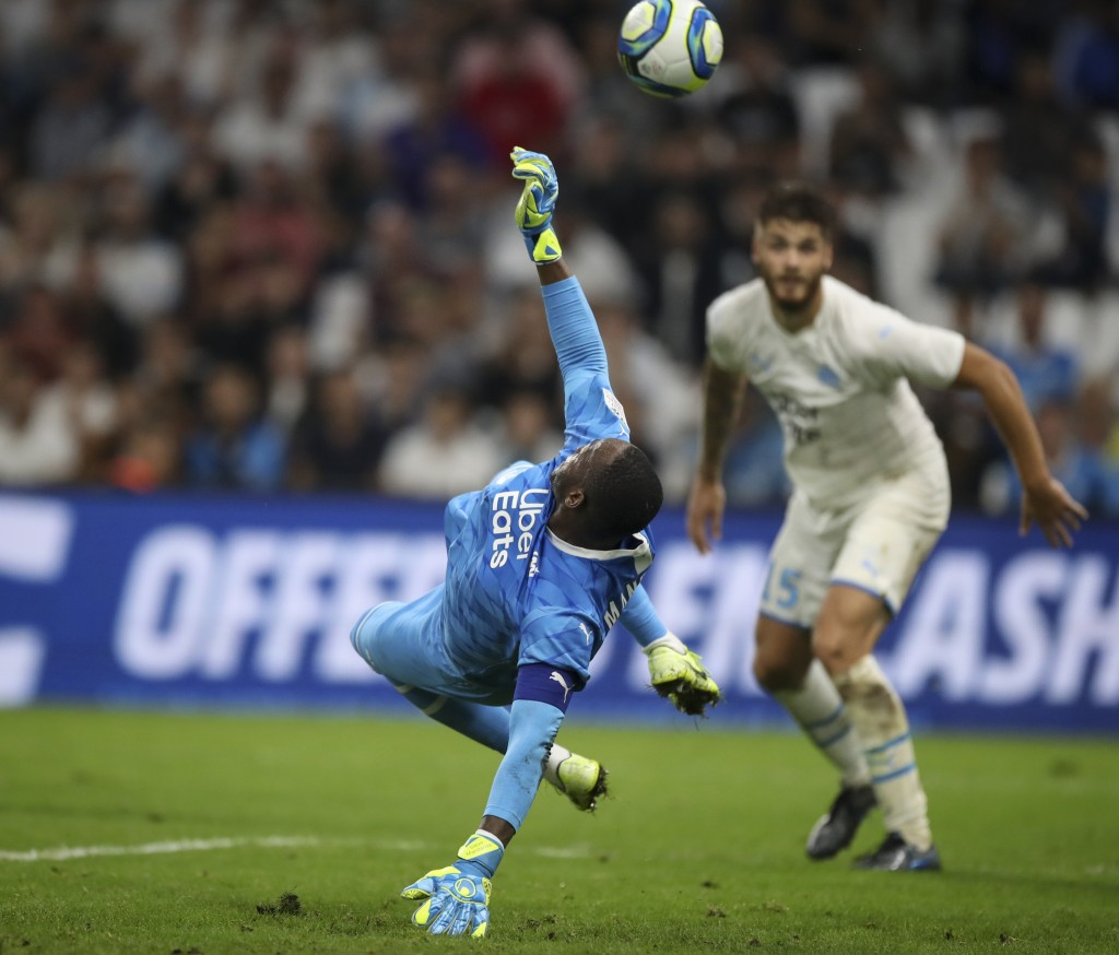 Marseille's goalkeeper Steve Mandanda saves a goal during the second half of the French League One soccer match between Marseille and Rennes at the Ve...