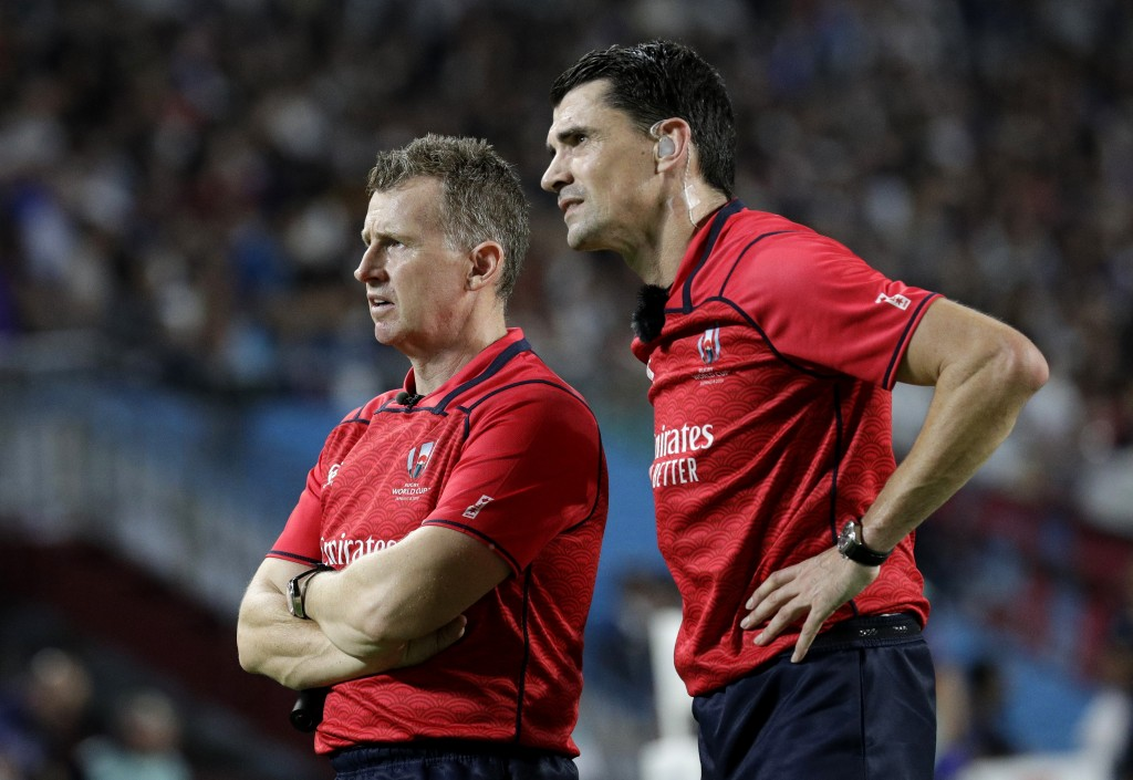 Referee Pascal Gauzere and and assistant Nigel Owens, left, watch a video review before awarding Scotland a penalty try during the Rugby World Cup Poo...