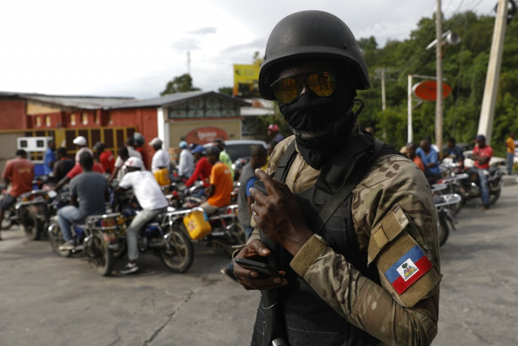 A police officer walks at a gas station where car and motorcycle drivers waited in lines of more than an hour to fill their tanks, in Port-au-Prince, ...