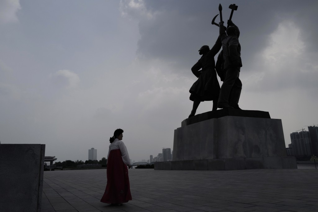 In this July 15, 2019, photo, a North Korean tourist guide walks past a statue in front of the Tower of Juche Idea in Pyongyang, North Korea. The word...