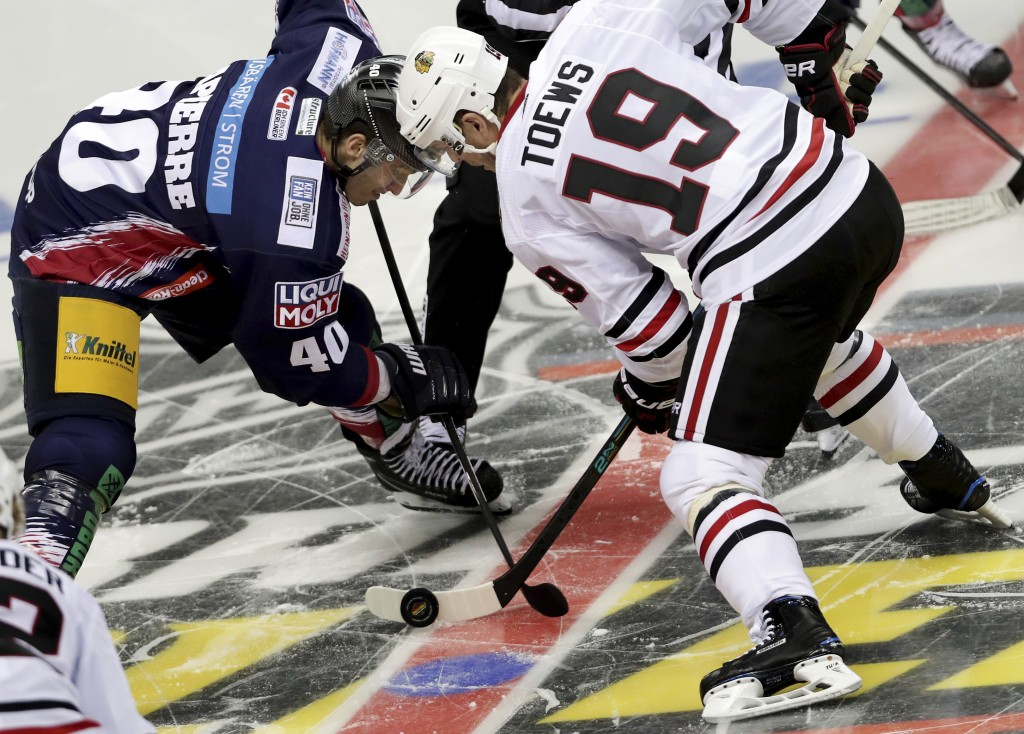Berlin's Maxim Lapierre, , left, and Chicago's Jonathan Toews, right, challenge for the puck during a NHL Global Series ice hockey game between Eisbae...