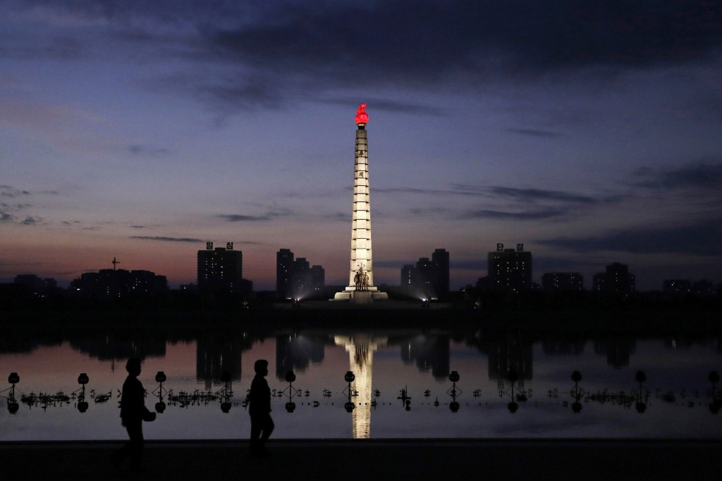 In this Sept. 15, 2018, photo, North Koreans take a walk at dawn by the Tower of Juche Idea in Pyongyang, North Korea. The word Juche is splashed acro...