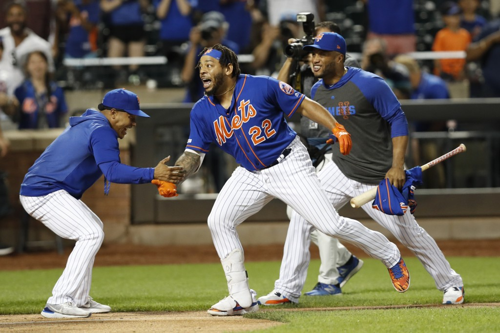 New York Mets' Marcus Stroman, left, greets Dominic Smith (22) at the plate after Smith hit a walk-off, solo home run in a baseball game against the A...