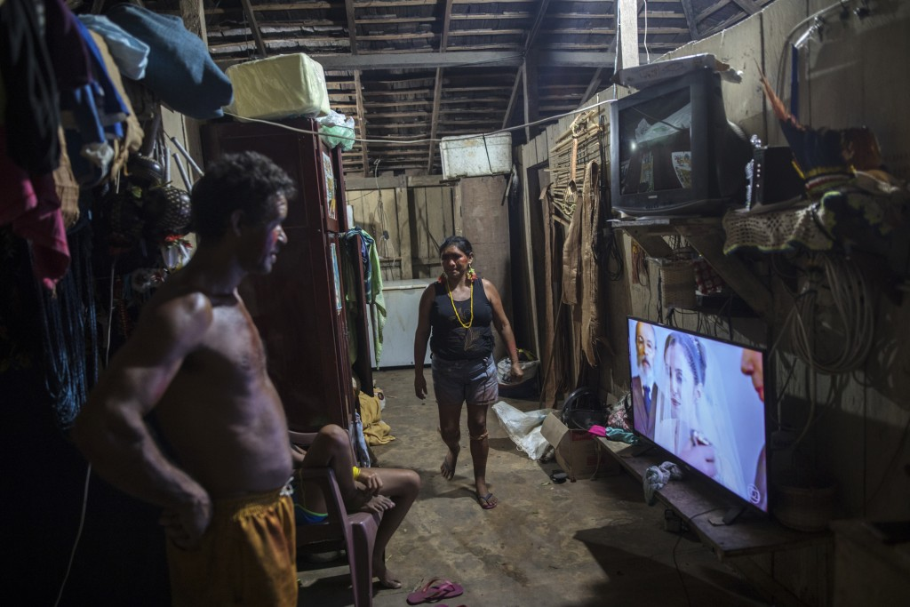 In this Sept. 4, 2019 photo, villagers watch a soap opera in their home in the village Tekohaw, in Para state, Brazil. Daily life in the remote Tembe ...