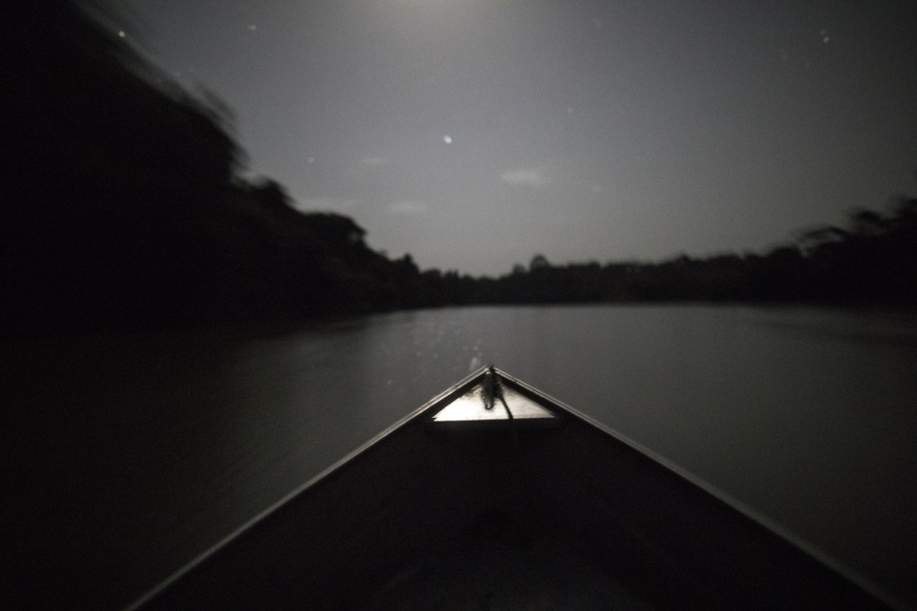 In this Sept. 3, 2019 photo, moonlight illuminates the bow of a boat transporting indigenous leaders back to their villages after a gathering of Tembe...