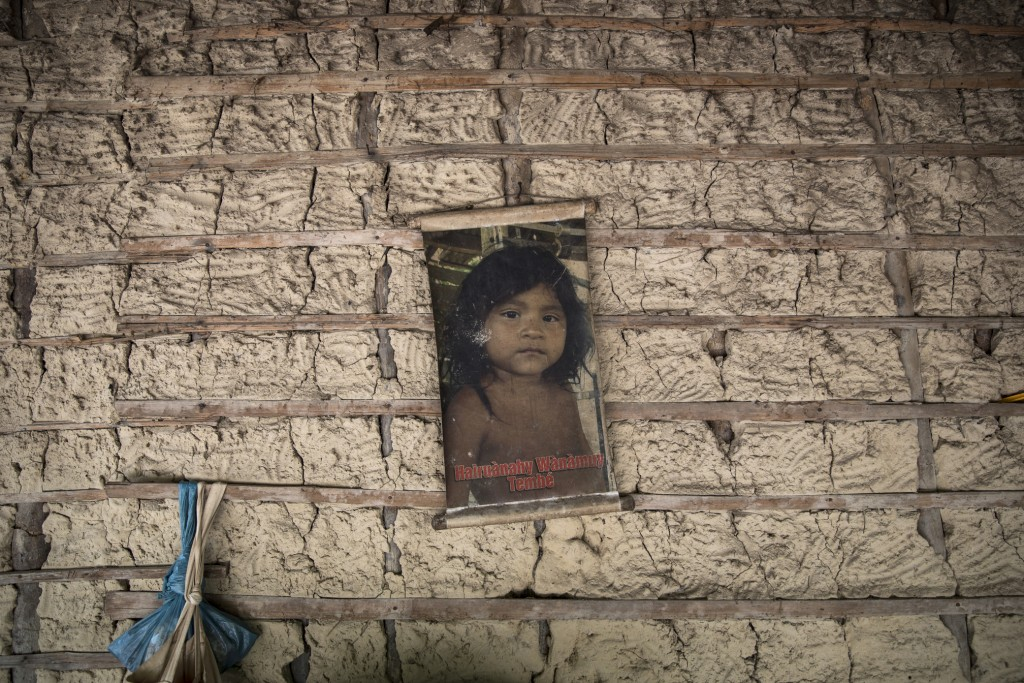 In this Sept. 2, 2019 photo, the image of a child hangs on an adobe wall inside her home in the Ka 'a kyr village, Para state, Brazil. Brazil's Presid...