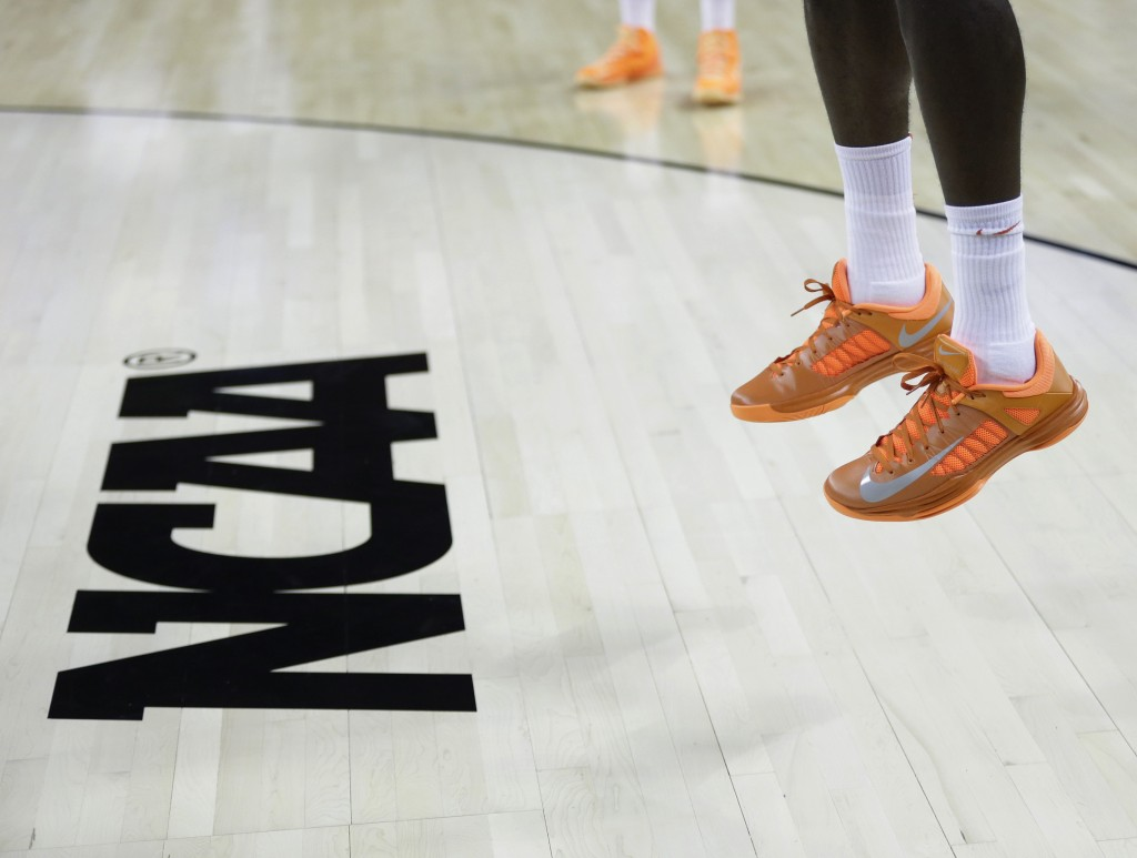 FILE - In this March 21, 2013, file photo, an athlete jumps near the NCAA logo during practice for a second-round game of the NCAA college basketball ...