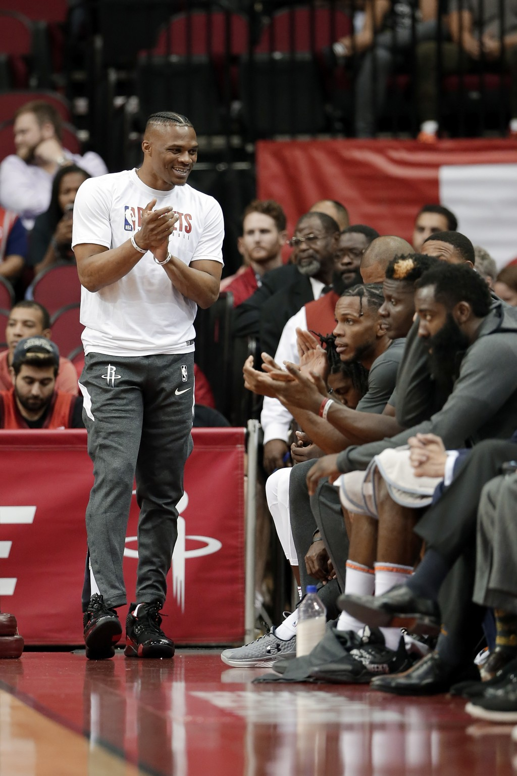 Houston Rockets guard Russell Westbrook, left, celebrates a score from the bench as he sits out an NBA basketball preseason game against the Shanghai ...