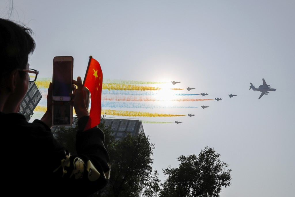 Chinese military planesfly in formation past the sun during a parade on Oct. 1, 2019.