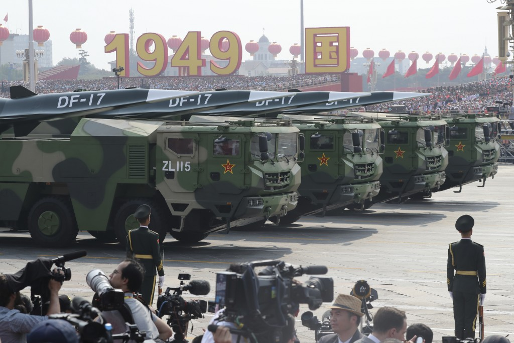 Military vehicles, carrying DF-17, roll down as members of a Chinese military honor guard march during the parade to commemorate the 70th anniversary ...