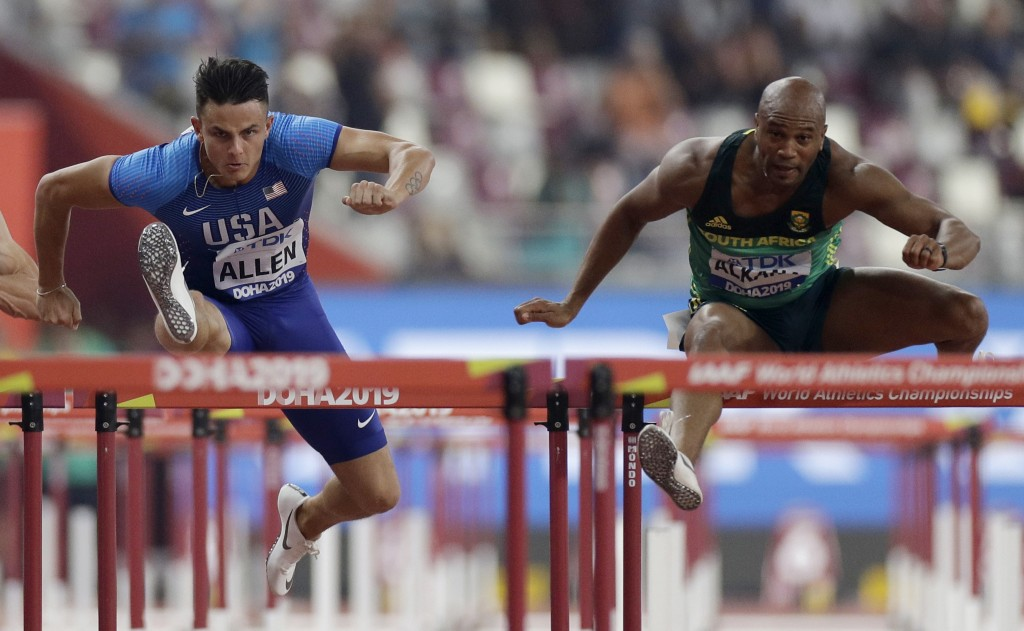 Devon Allen, of the United States, left, and Antonio Alkana, of South Africa, compete in the men's 110 meter hurdles heats at the World Athletics Cham...