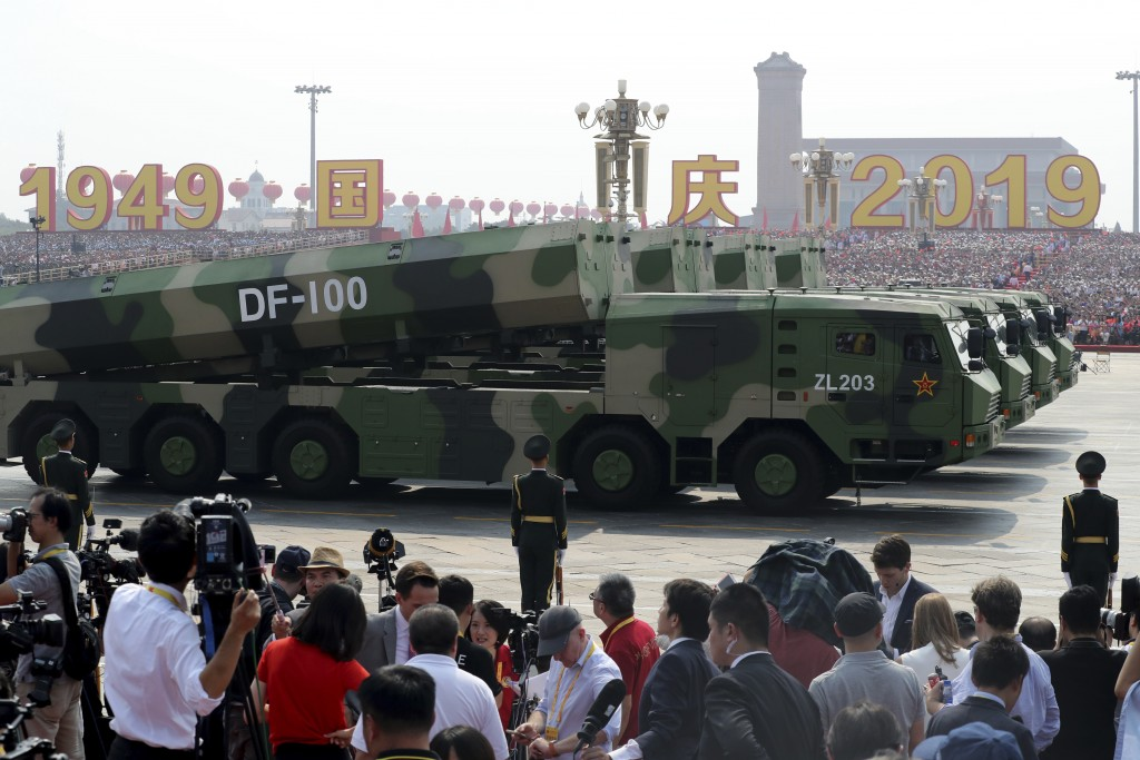 Military vehicles carrying DF-100 roll down as members of a Chinese military honor guard march during the celebration to commemorate the 70th annivers...