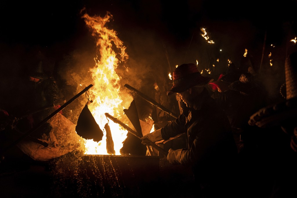 In this Saturday, Sept. 27, 2019 photo, villagers take part in the procession of El Vítor in the town of Mayorga, northwest Spain. Yielding burning wi...