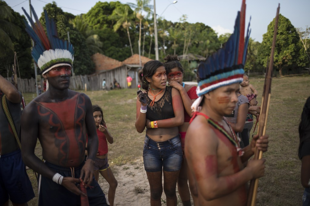 In this Sept. 3, 2019 photo, people gather for a meeting of the Tembe tribes in the Tekohaw village, in Para state, Brazil. Under a thatch-roof shelte...