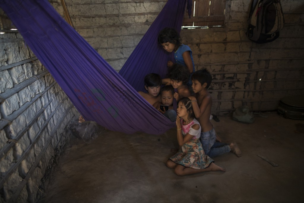 In this Sept. 2, 2019 photo, siblings and cousins gather around a cellphone on a purple hammock to watch a children's cartoon on YouTube, in the home ...