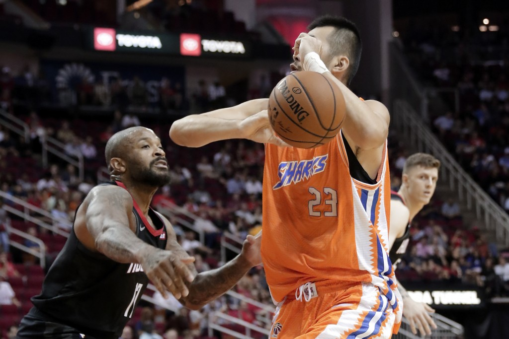 Houston Rockets forward P.J. Tucker, left, knocks the ball away from Shanghai Sharks center Zhang Zhaoxu (23) during the first half of an NBA basketba...
