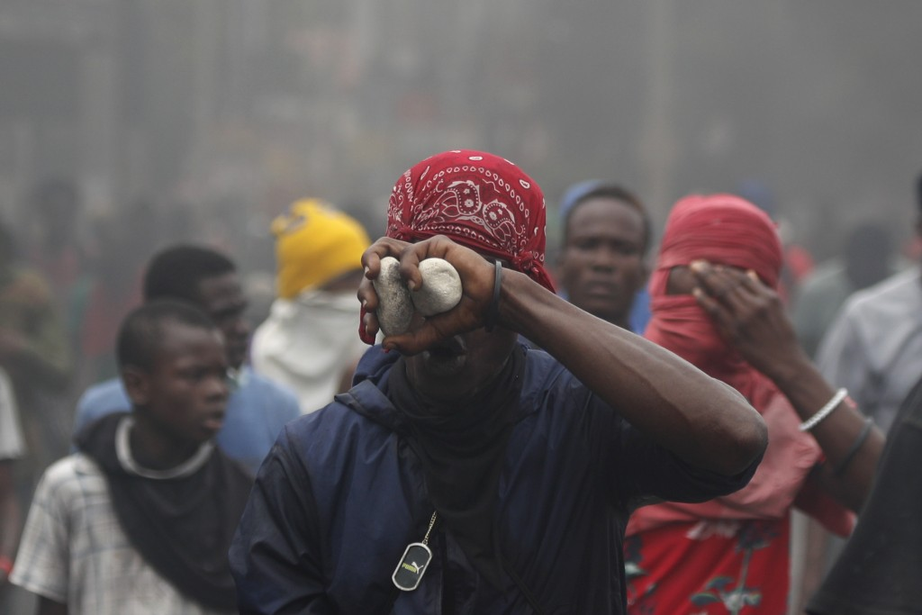 A man hides his face behind rocks as opposition protestors march, calling for Haitian President Jovenel Moise to resign in Port-au-Prince, Haiti, Mond...