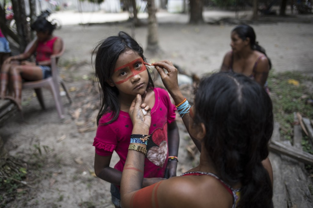 In this Sept. 4, 2019 photo, a child stands still as a woman paints a red mask around her eyes, in preparation for a gathering of tribes in the Alto R...
