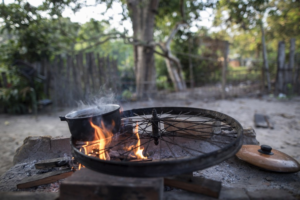 In this Sept. 5, 2019 photo, a Tembe family cooks breakfast asa pot boils on top of a bicycle wheel serving as a grill outside their home in the Tekoh...