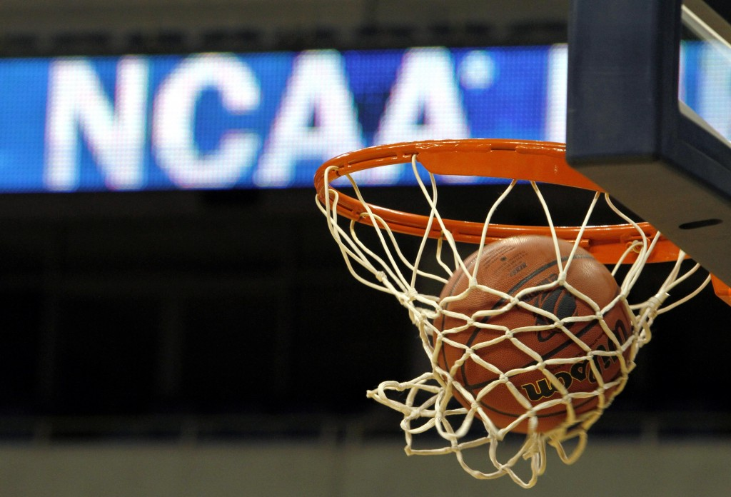 FILE - In this March 20, 2010, file photo, a ball flicks through the net in front of the NCAA logo on the marquis during an NCAA college basketball pr...