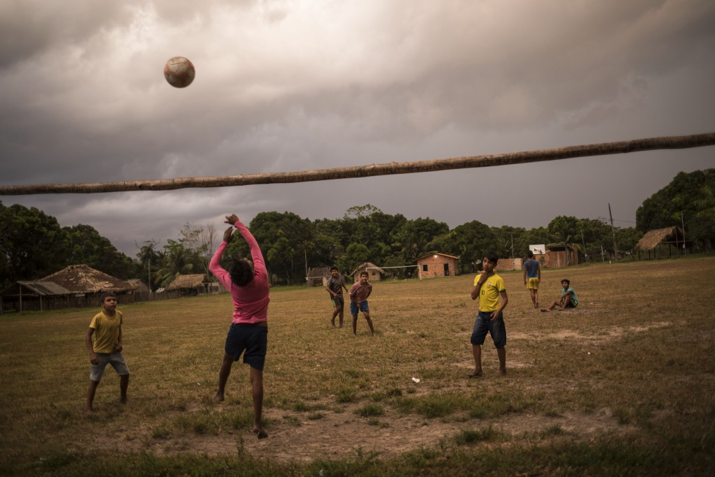 In this Sept. 2, 2019 photo, Tembe boys play soccer on a field in the Cajueiro village, Para state, Brazil. During the rite of passage into adulthood,...