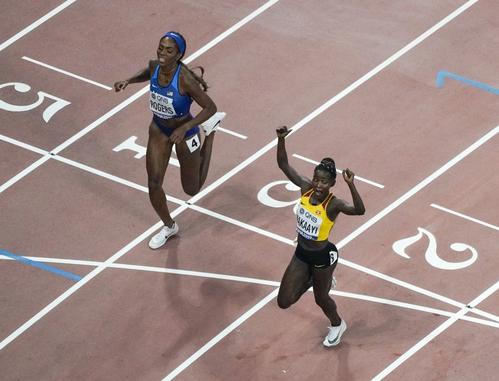 Halimah Nakaayi, of Uganda, reacts in front of Raevyn Rogers, of the United States, as she wins the women's 800 meter final at the World Athletics Cha...