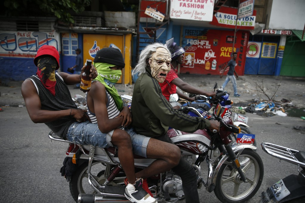 Masked protestors ride a motorcycle in Port-au-Prince, Haiti, Monday, Sept. 30, 2019. Demonstrators set fires Monday and chanted calls for Haiti's Pre...