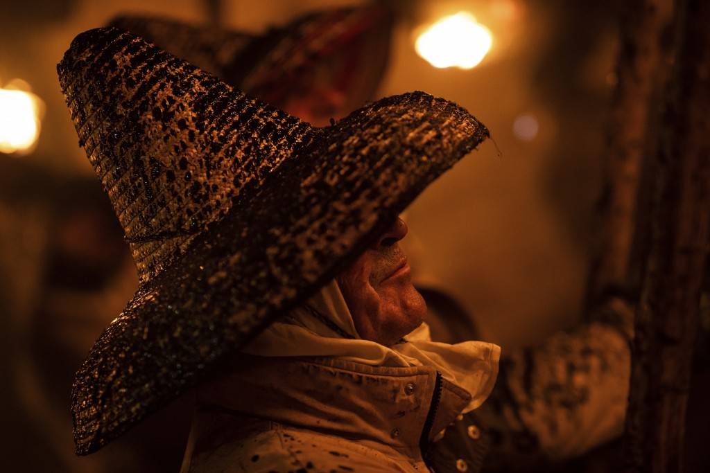 In this Saturday, Sept. 27, 2019 photo, a villager dressed up in old clothes and wearing a hay hat takes part in the procession of El Vítor in the tow...