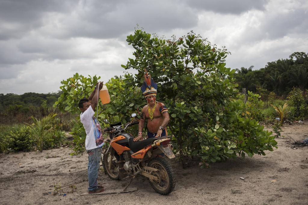 "In this Sept. 4, 2019 photo, Cajueiro chieftain Sergio Muxi Tembe, stand by as the tank of his motorcycle is filled with gas, in Para state, Brazil. ""..."