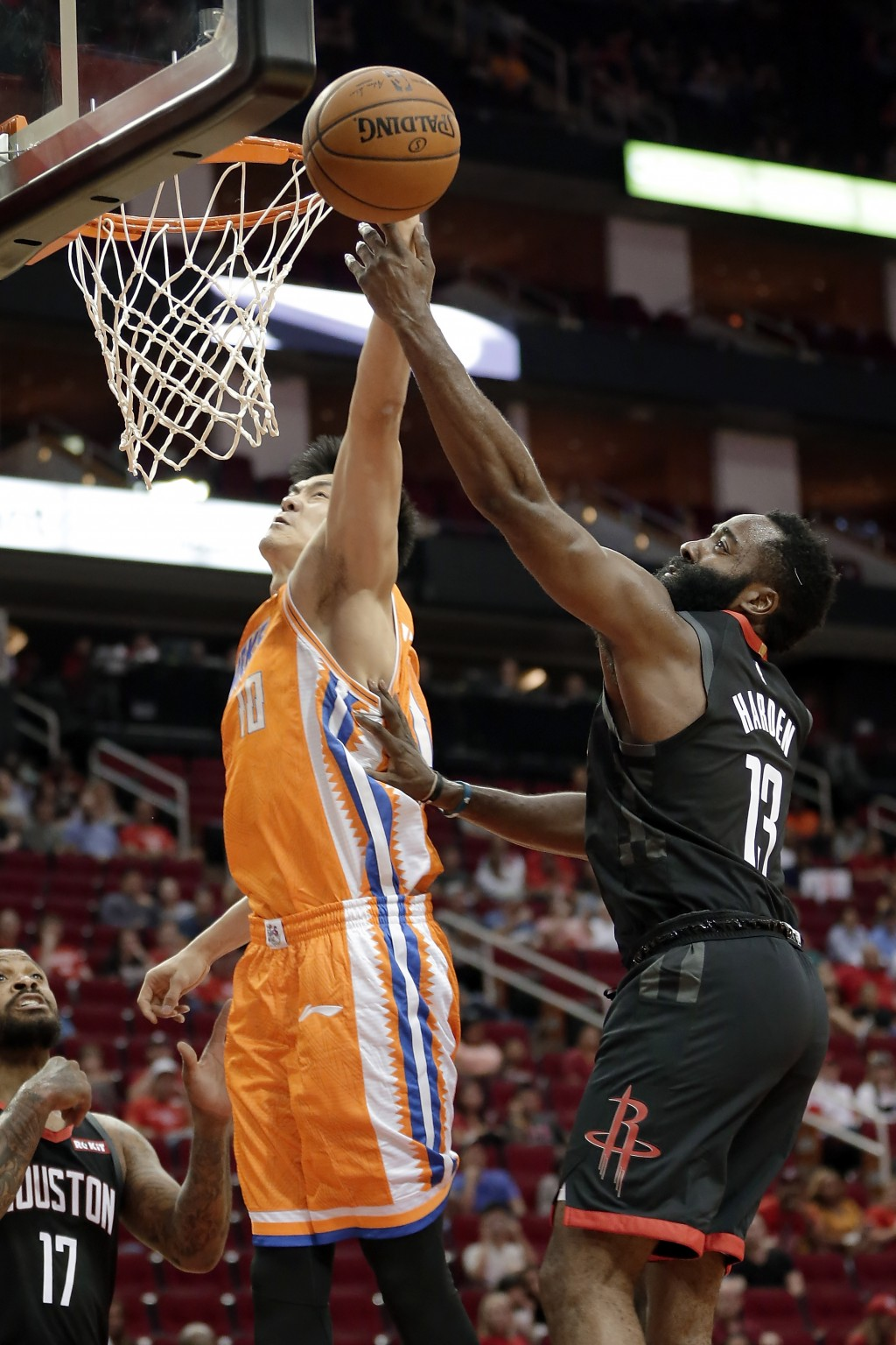 Shanghai Sharks center Dong Hanlin (10) is fouled on his layup by Houston Rockets guard James Harden (13) during the first half of an NBA basketball p...