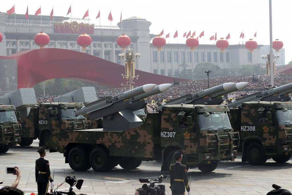 Military vehicles roll down as members of a Chinese military honor guard march during the celebration to commemorate the 70th anniversary of the found...