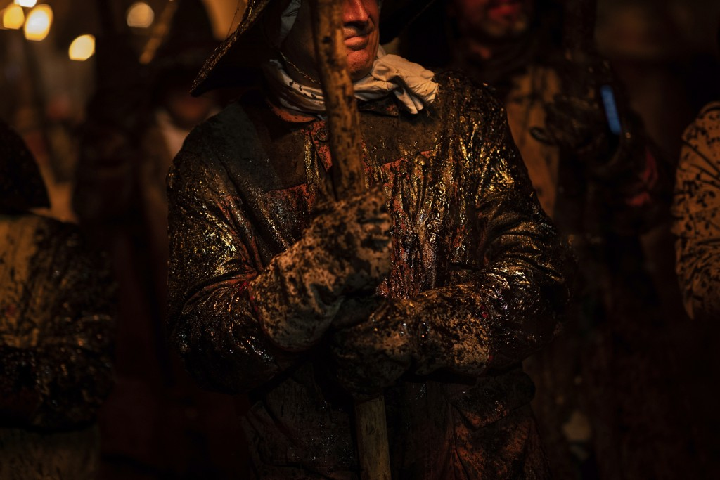 In this Saturday, Sept. 27, 2019 photo, a villager covered in tar takes part in the procession of El Vítor in the town of Mayorga, northwest Spain. Th...