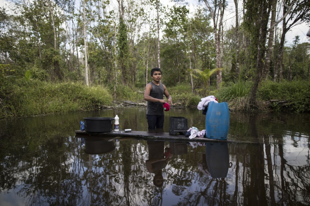 In this Sept. 2, 2019 photo, a young man washes his clothes in a pond in the viallge Ka 'a kyr, in Para state, Brazil. Villages along the Guama and Gu...