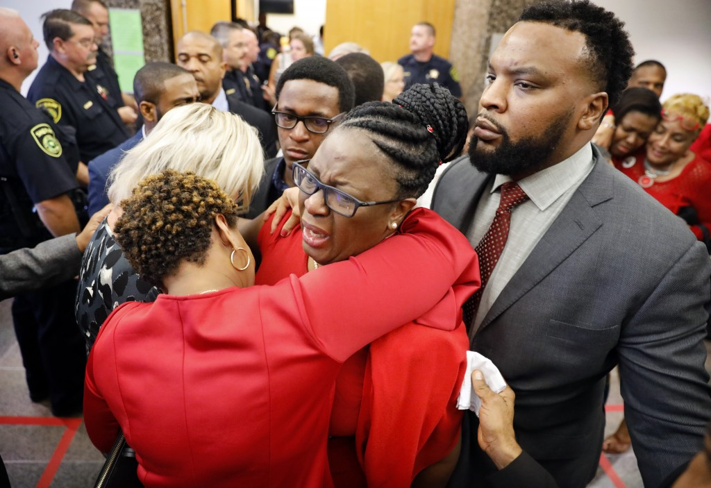 Botham Jean's mother, Allison Jean, center, escorted by civil rights attorney Lee Merritt, right,, is hugged by family members outside the courtroom a...
