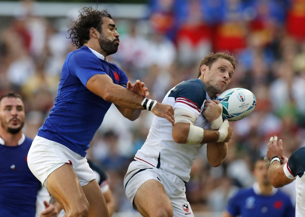 France's Yoann Huget, left, and United States' Blaine Scully battle for the ball during the Rugby World Cup Pool C game at Fukuoka Hakatanomori Stadiu...