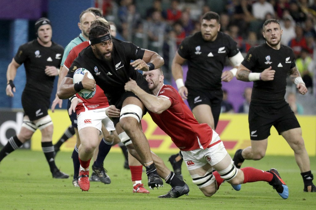 New Zealand's Patrick Tuipulotu is tackled by a Canadian defender during the Rugby World Cup Pool B game at Oita Stadium between New Zealand and Canad...