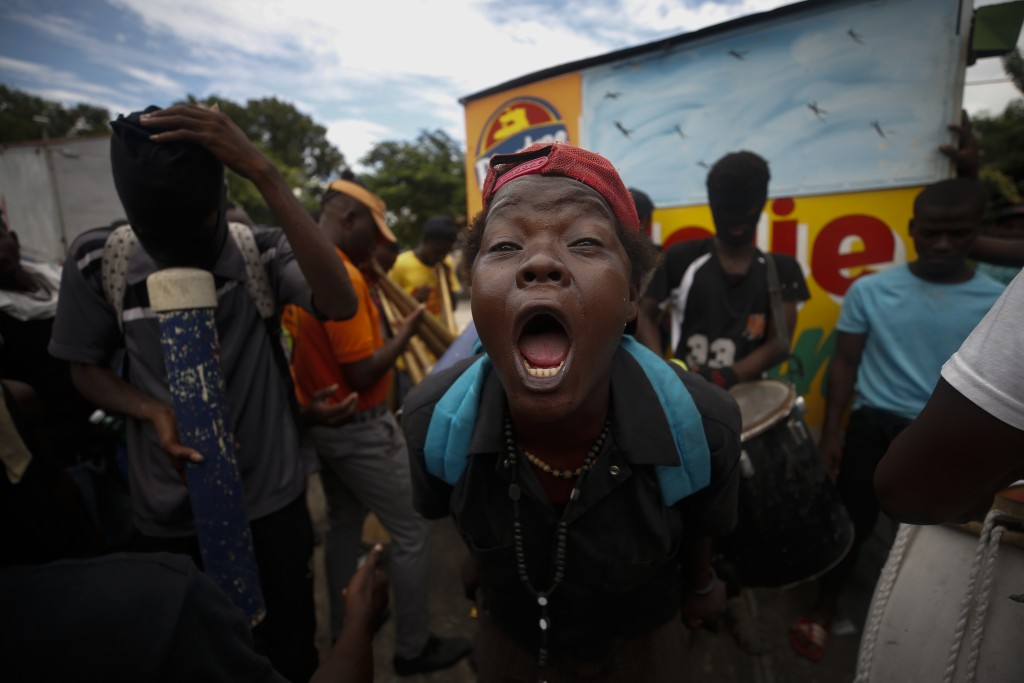 A woman shouts that Haitian President Jovenel Moise has to leave office as protestors play music in a park outside the National Palace in Port-au-Prin...