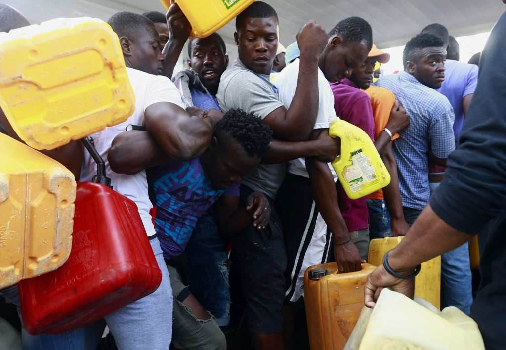 FILE - In this Sept. 4, 2019 file photo, people fight as they line up at a closed gas station, hoping it will open eventually, during a fuel shortage ...