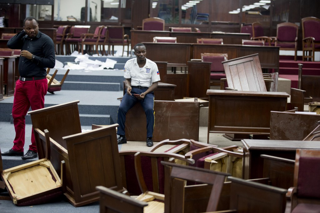 FILE - In this Sept. 3, 2019 file photo, a security officer sits amid overturned tables inside Parliament after it was vandalized in Port-au-Prince, H...