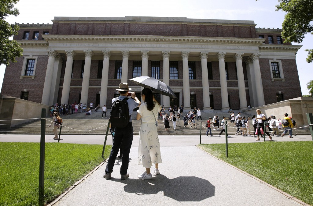 FILE - In this July 16, 2019, file photo, people stop to record images of Widener Library on the campus of Harvard University in Cambridge, Mass. U.S.