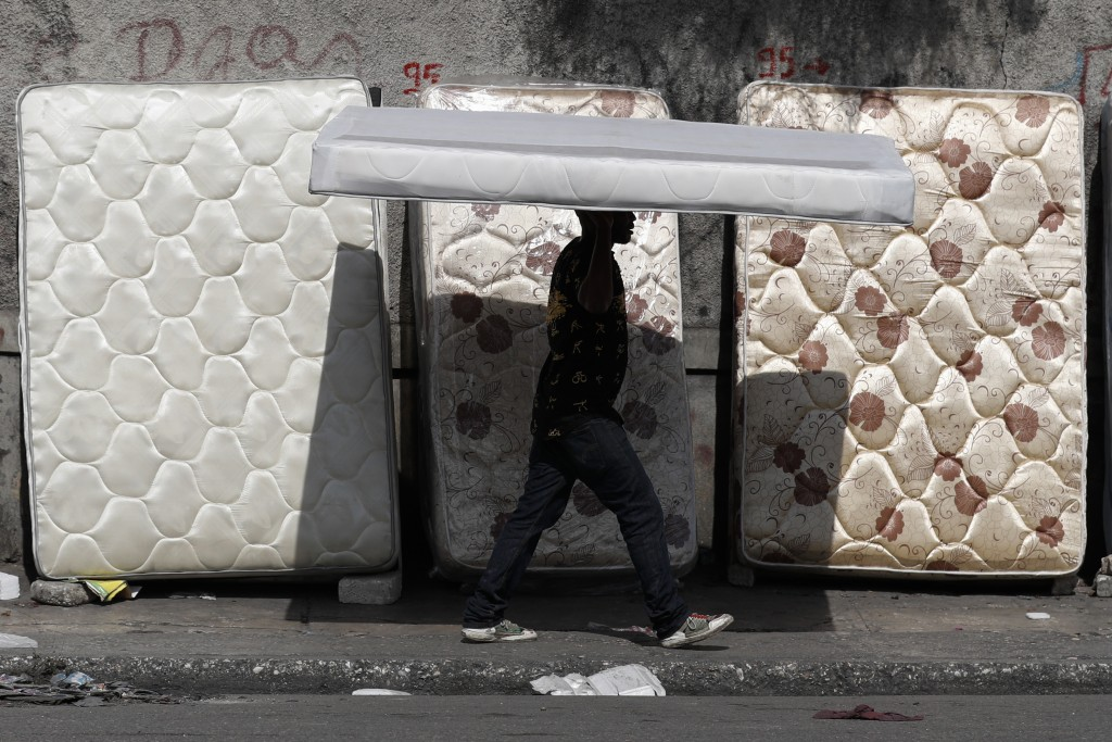 A man balances a mattress on his head past others leaned up for sale alongside a road in Port-au-Prince, Haiti, Wednesday, Oct. 2, 2019. There was a r...