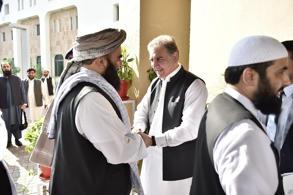 In this photo released by the Foreign Office, Pakistan's Foreign Minister Shah Mehmood Qureshi, center, receives members of Taliban delegation at the ...